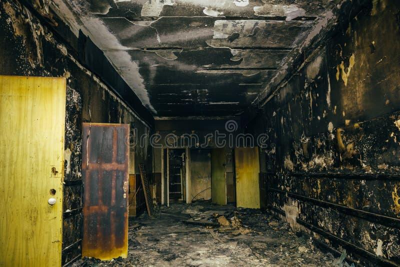Brûlé par l'intérieur du feu du vieux bâtiment Murs carbonisés de cendre, portes et meubles endommagés image libre de droits