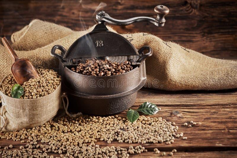 Brûleur de café de fonte de vintage avec les haricots crus photographie stock libre de droits
