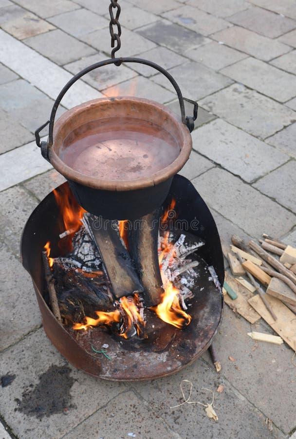 brûlures de cuivre antiques de chaudron au-dessus d'un feu image stock