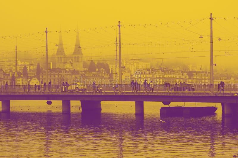 Brücke in Luzern im Nebel, die Schweiz-Winterzeit Decemper 2017 Gelbes und violettes duotone lizenzfreie stockfotos