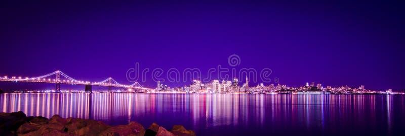 Brücke und Stadt der Leuchten an der Nacht u. an der Reflexion stockbilder