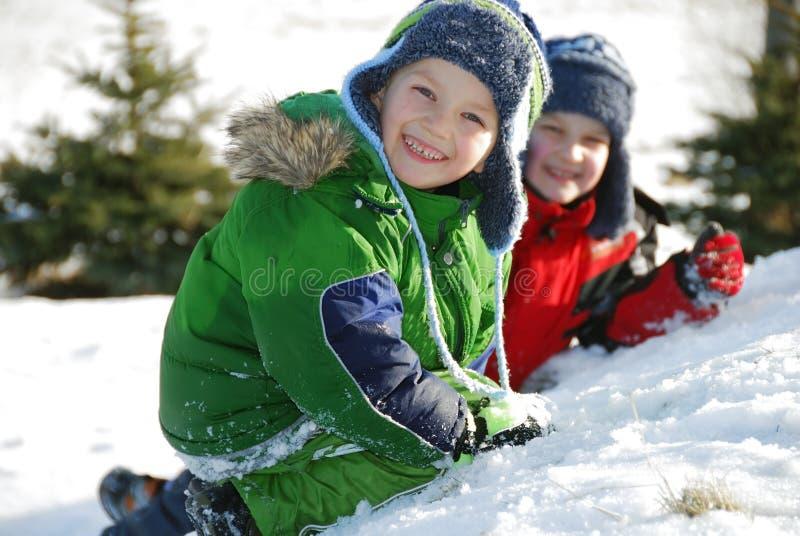 Brüder, die im Schnee spielen lizenzfreie stockfotos