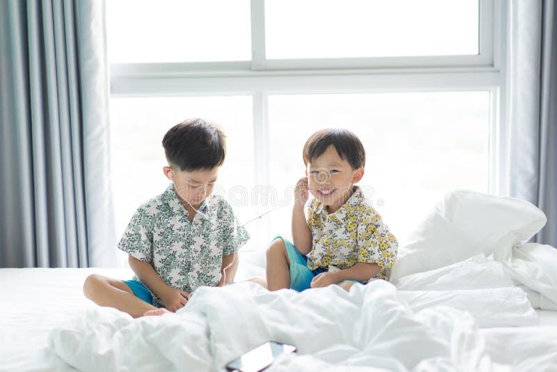 Brüder hören das Lied mit Handy morgens auf dem Bett lizenzfreie stockbilder