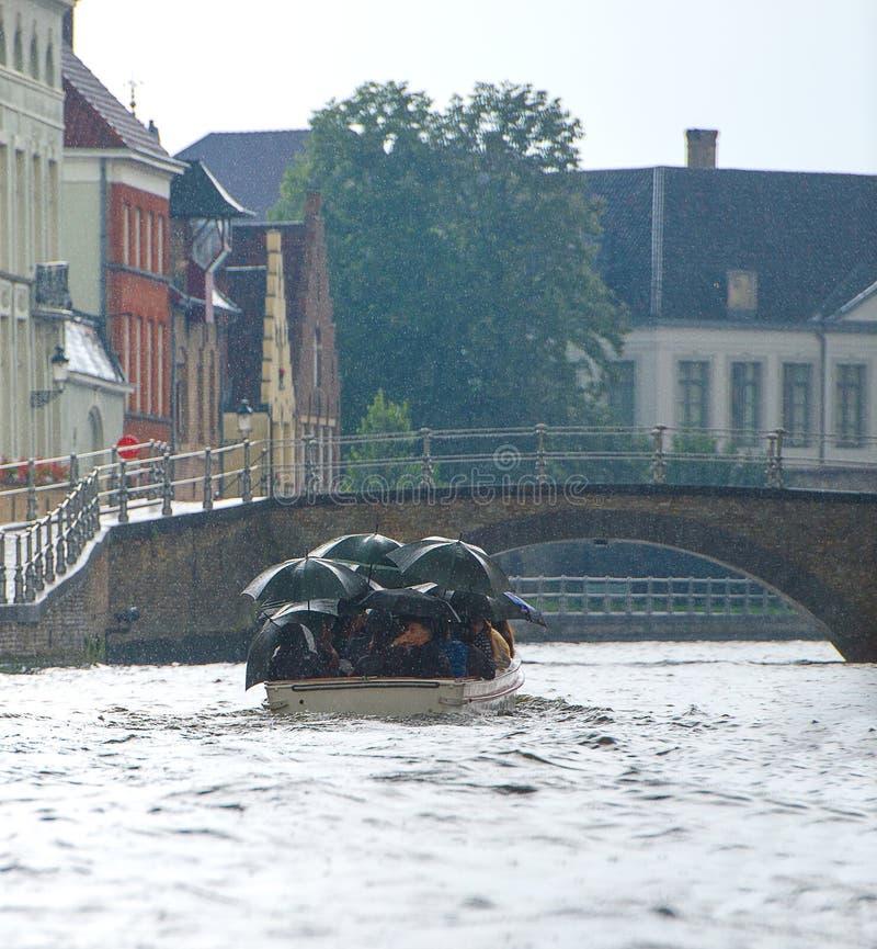 BRÜGGE, BELGIEN - 10. August 2017 Touristisches Boot auf Kanal in Brügge an einem regnerischen Tag lizenzfreie stockfotografie