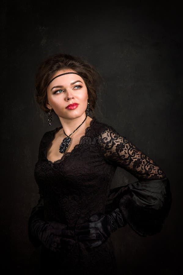 Brüllenzwanziger jahre Frauenporträt im Stil Gatsby Betrachten der Kamera Schöne junge Frau in einem schwarzen Kleid, Satinhandsc stockfotos