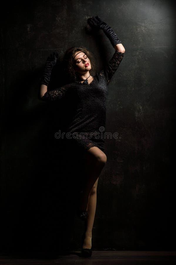 Brüllenzwanziger jahre Frauenporträt im Stil Gatsby Betrachten der Kamera Schöne junge Frau in einem schwarzen Kleid der Spitzes, lizenzfreie stockbilder