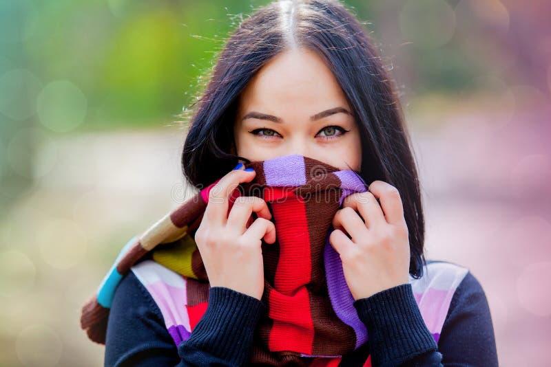 Brünettemädchen mit buntem Schal stockfoto