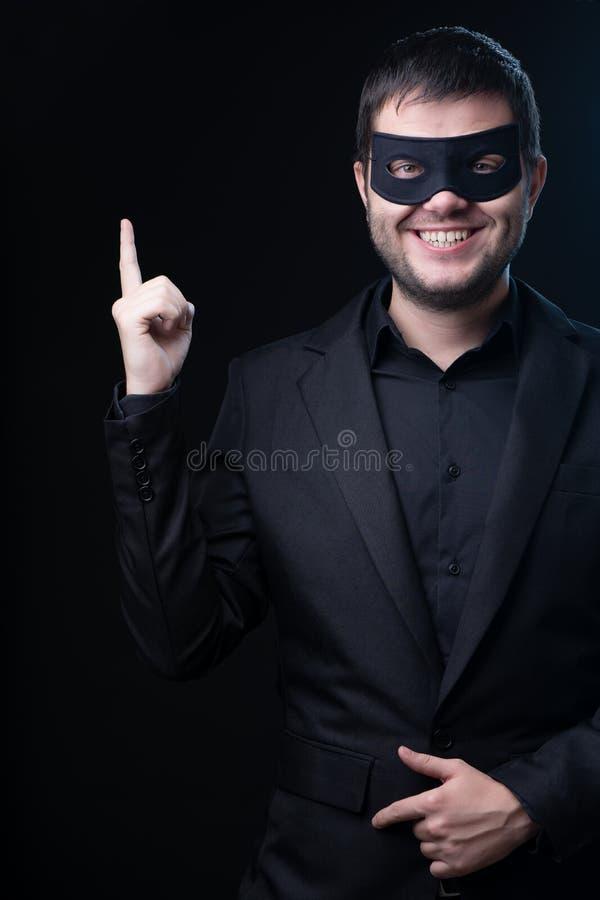 Brünettemann in der schwarzen Maske, Jacke auf leerem schwarzem Hintergrund lizenzfreies stockfoto
