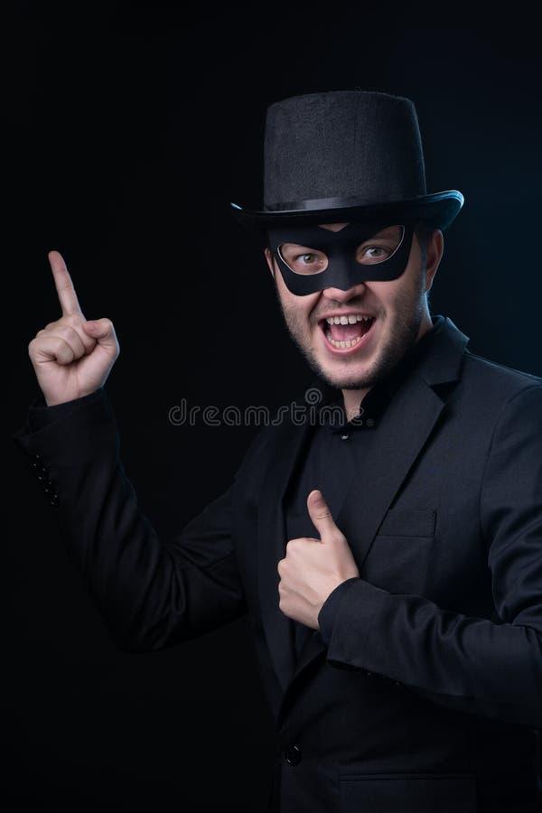 Brünettemann in der schwarzen Maske, Jacke, Hut auf leerem schwarzem Hintergrund lizenzfreie stockfotos