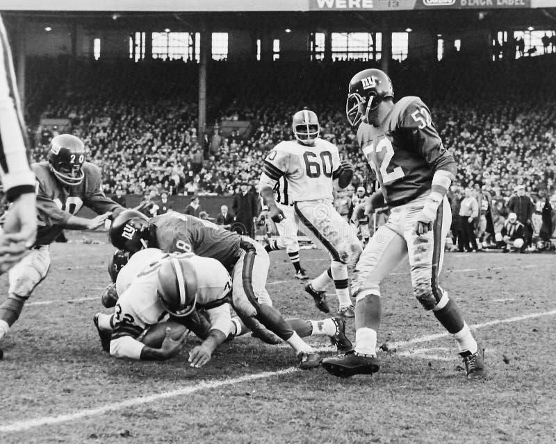 Brüniert Legende Jim Brown, der durch das NY Giants angepackt erhält stockfotografie