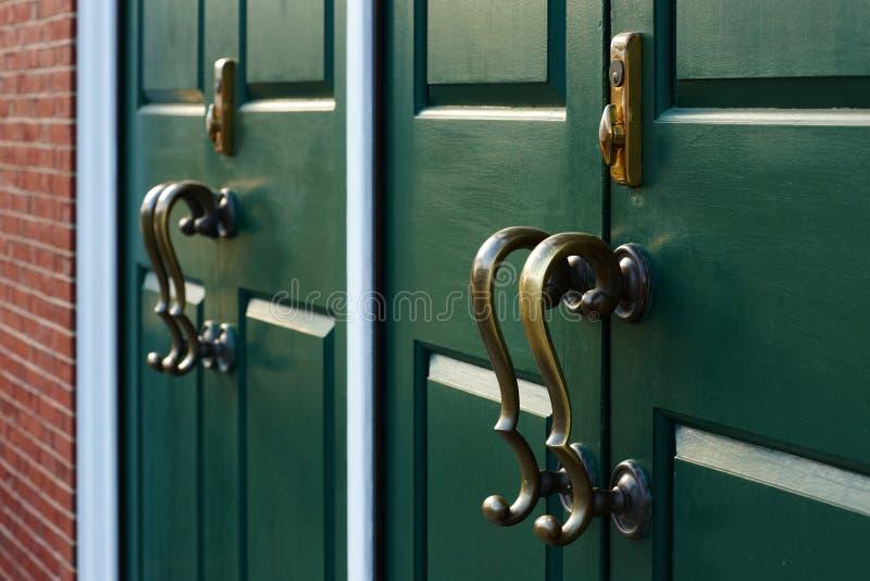 Brąz rękojeści ciskają cienie na zielonym drzwi 2011 02 04 zdjęcia royalty free