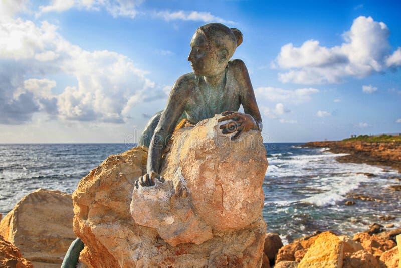 Brązowa statua kobieta dzwoniący ` zol Zmienia ` na kamieniu, Paphos, Cy zdjęcie stock