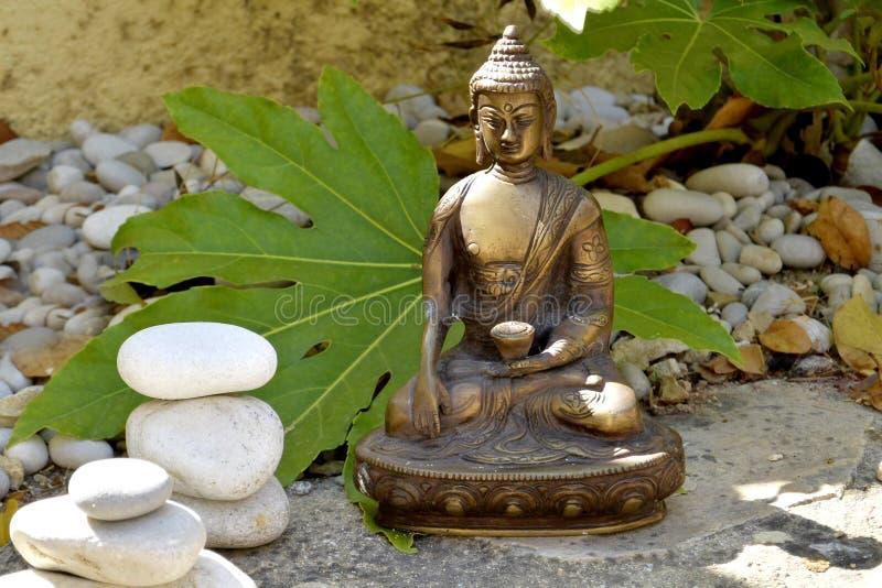 Brązowa statua macanie ziemia Buddha z zrównoważonymi kamieniami zdjęcia stock
