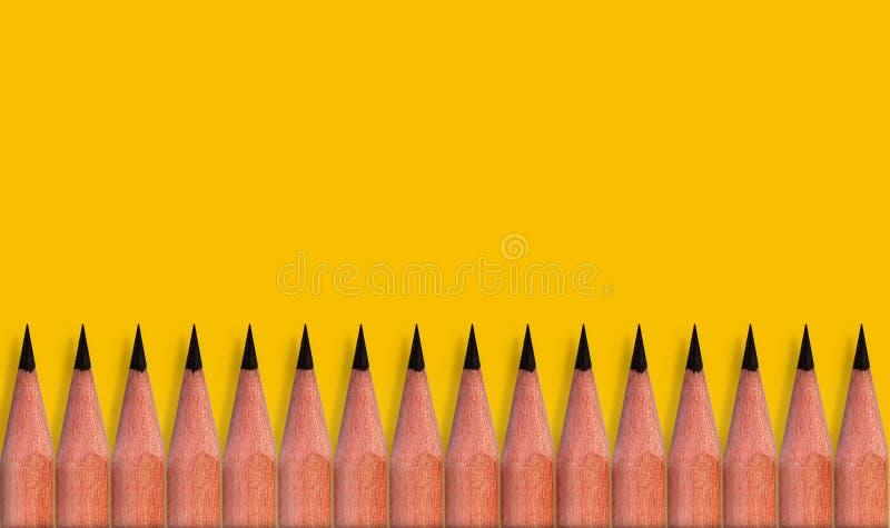 Brązowe ołówki umieszczane na żółtym kolorowym tle papieru z przestrzenią do kopiowania obrazu lub tekstu zdjęcie stock