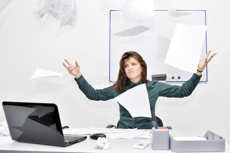 Brązowowłosa dziewczyna w biurze w oburzeniu rzucał up papiery i dokumenty fotografia stock