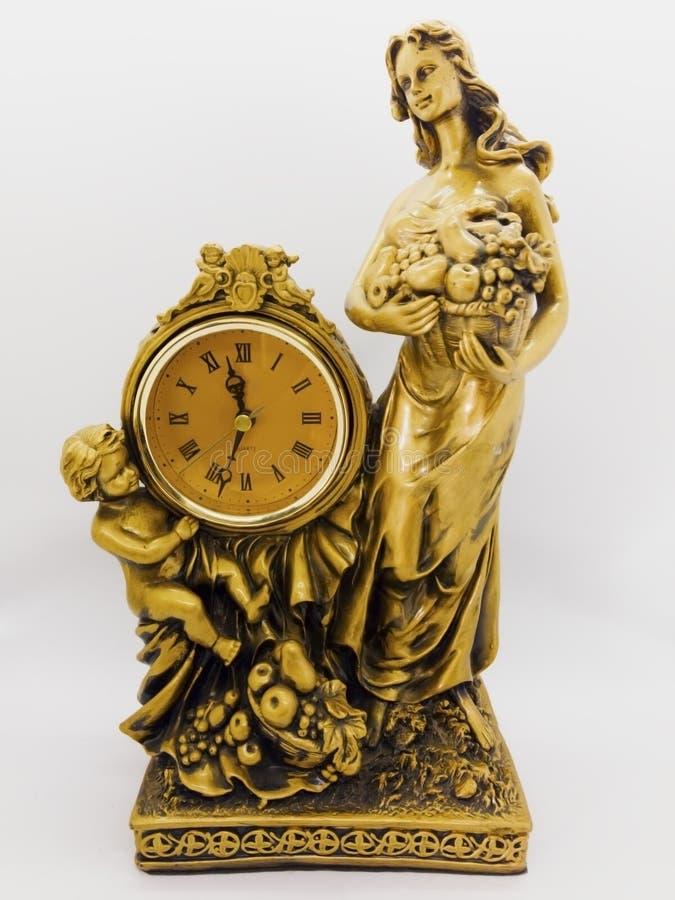 Brązowy biurko zegar, kobieta trzyma owocowego kosz chłopiec i obrazy stock