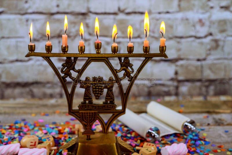 Brązowy Hanukkah menorah z płonącymi świeczkami na drewnianego stołu przodu rocznika betonowej ściany starym tle obrazy royalty free