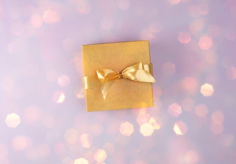 brązu papierowy pudełko z łękiem na purpurowym tle z błyszczącym żółtym bokeh obrazy royalty free