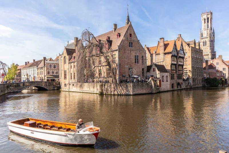 Br?gge, Belgien - 5. APRIL 2019: Ausflugboot, das Touristen durch die sch?ne Stadt von Br?gge durch den Kanal nimmt stockbilder