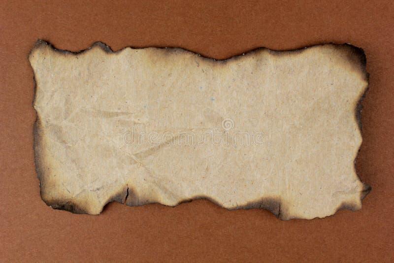 Brûlé de papier sur le fond brun images libres de droits