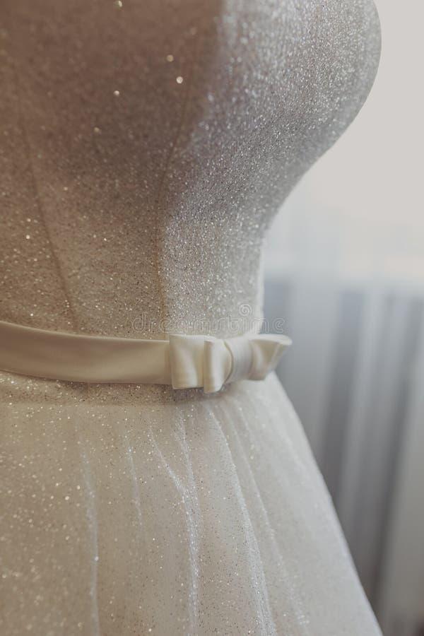 br?llop f?r kl?nningfragmentbest?llning Vit br?llopskl?nning med en full kjol p? en h?ngare i rummet av bruden med vita gardiner  royaltyfri foto