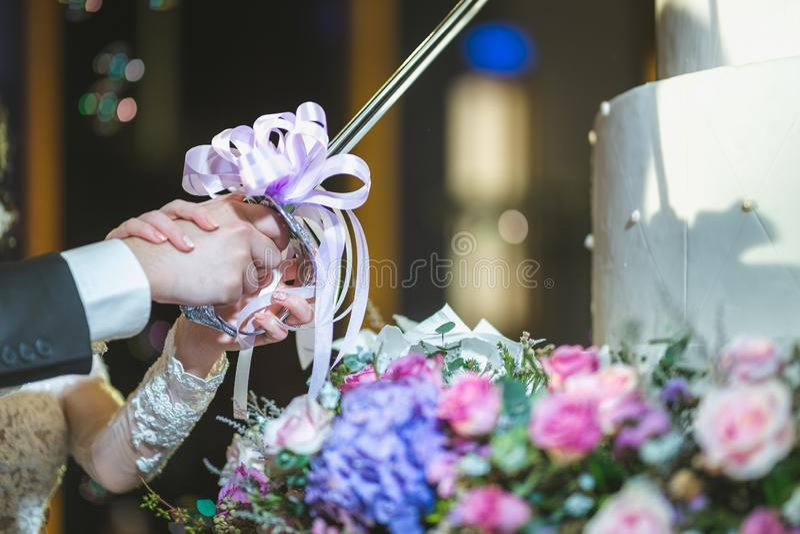 br?llop f?r 8 pie ursnygg brud och stilfull brudgum som klipper den stilfulla br?llopst?rtan med blommor p? br?llopmottagandet i  royaltyfri foto