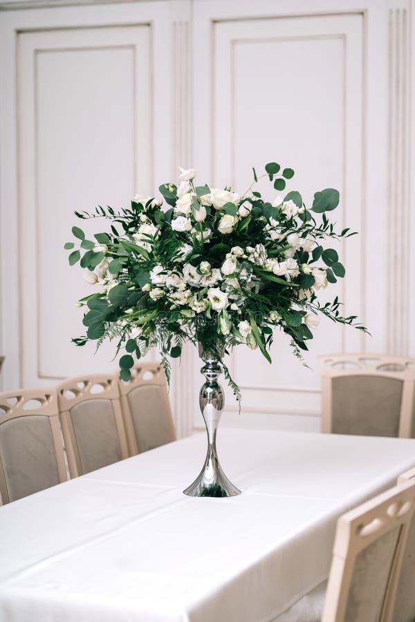 Br?llopdekoren, tillbeh?r, orkid?r, rosor, eukalyptuns, en bukett i en restaurang, presiderar tabellinst?llningen arkivbild