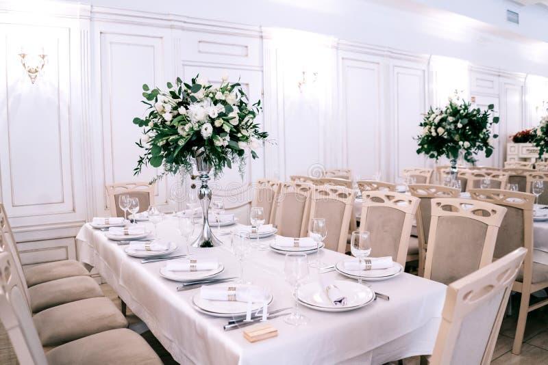 Br?llopdekoren, tillbeh?r, orkid?r, rosor, eukalyptuns, en bukett i en restaurang, presiderar tabellinst?llningen royaltyfri foto