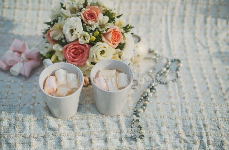 Br?llopfotografi gifta sig övervintrar detaljer bröllop två koppar med och marshmallower, en brud- bukett och vigselringar royaltyfria bilder