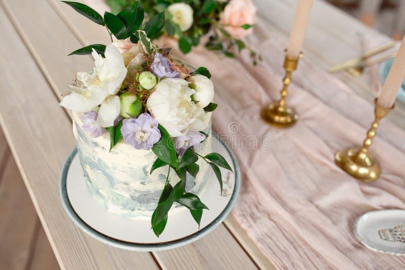 Br?llopgarneringtabell i tr?dg?rden, blom- ordning, i stiltappningen p? utomhus- caken blommar br?llop dekorerat royaltyfria foton