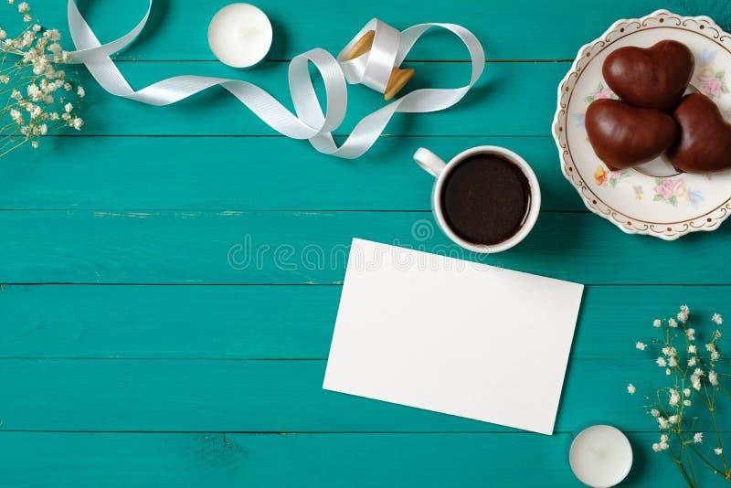 Br?llopinbjudanbegrepp Tomt pappers- kort med tusensk?nablommor, hj?rta-formad choklad och kaffekoppen p? gr?n tr?bakgrund arkivfoton