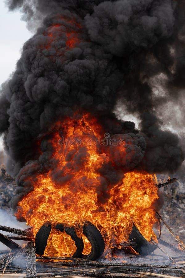 Br?nnande bilgummihjul, stark flamma av r?d brand och moln av svarta dunster arkivfoto