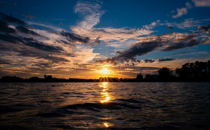 Br?nnhet orange solnedg?nghimmel H?rlig sky reflekterar ljust färgvatten för soluppgång arkivfoto