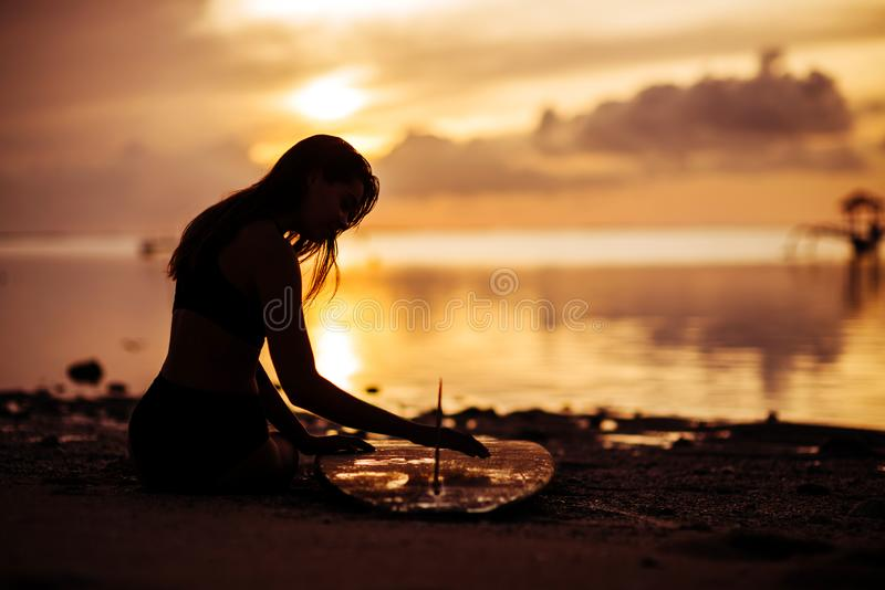Br?nningflicka med surfingbr?dan p? stranden arkivfoto