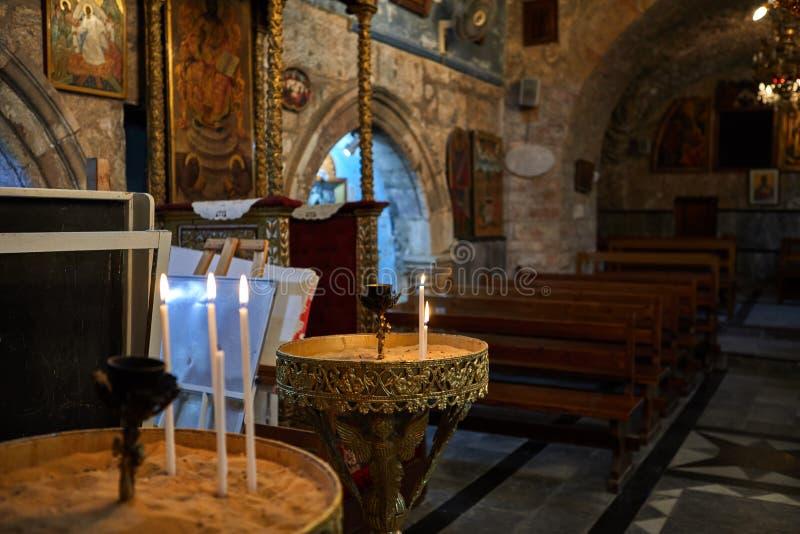 Br?nnskada f?r m?nga kyrklig stearinljus i m?rkret Stearinljus i kyrkan arkivfoto