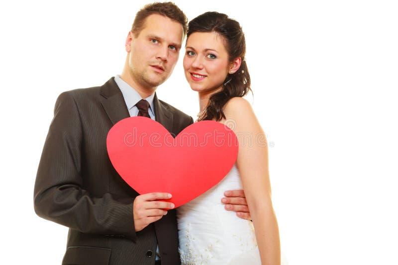 Br?utigam- und Brautpaare, die Herz halten stockfoto