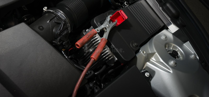 braçadeira vermelha na bateria de carro imagem de stock
