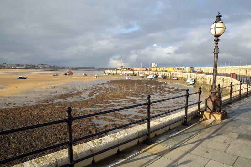 Braço do porto de Margate com barcos da amarração, o farol e a praia na maré baixa, Margate, Kent, Reino Unido imagem de stock
