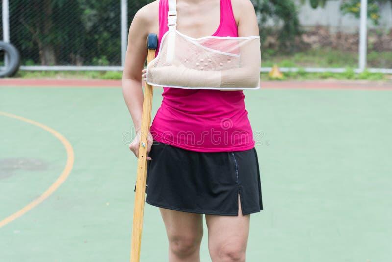 Braço doloroso vestindo ferido do sportswear da mulher com atadura da gaze foto de stock