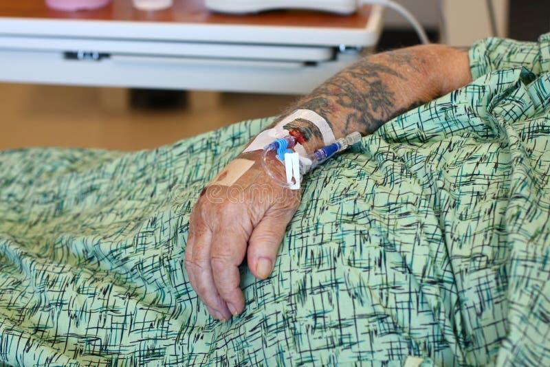 Braço masculino idoso de IV do paciente hospitalizado fotografia de stock