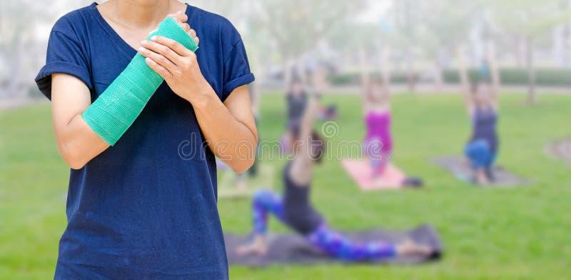 Braço quebrado com o molde do verde no grupo borrado da aptidão da mulher - ioga fotos de stock royalty free
