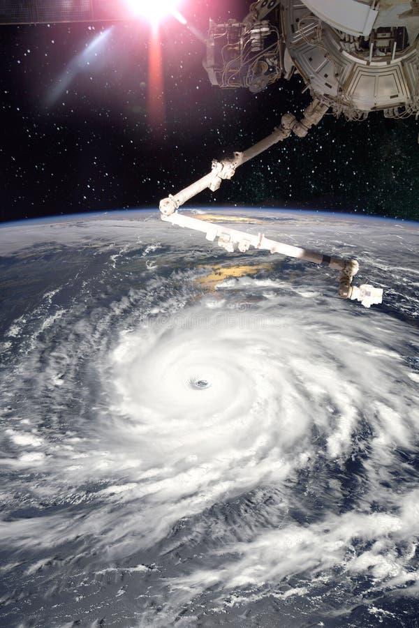 Braço robótico do ISS em um espaço e em um furacão na terra imagem de stock
