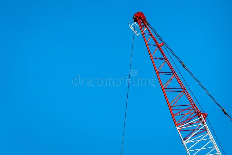 Braço vermelho e branco do guindaste contra o céu azul foto de stock