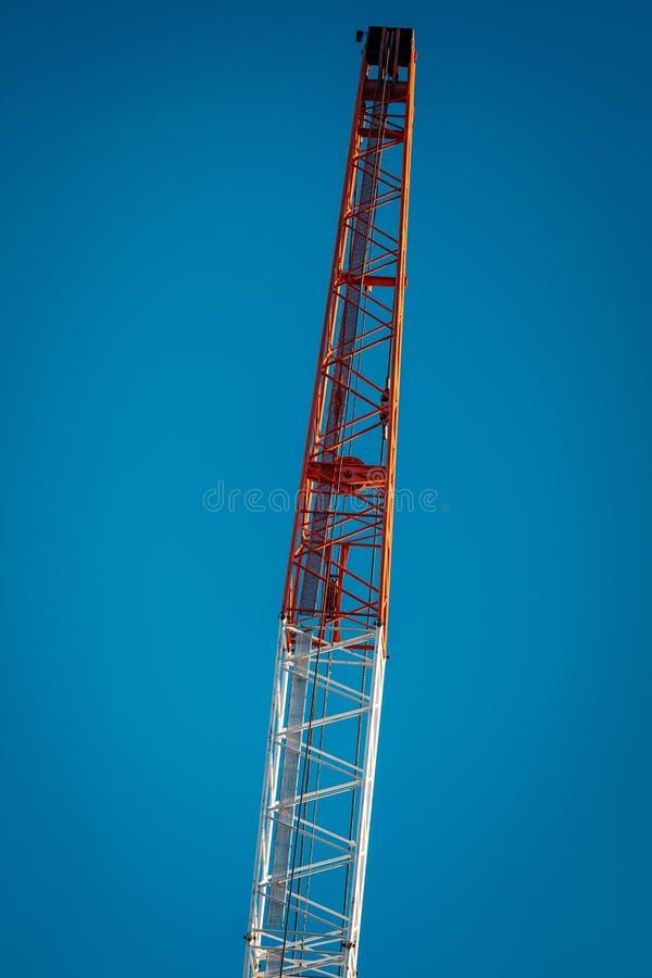 Braço vermelho e branco do guindaste quase vertical com fundo do céu azul fotos de stock