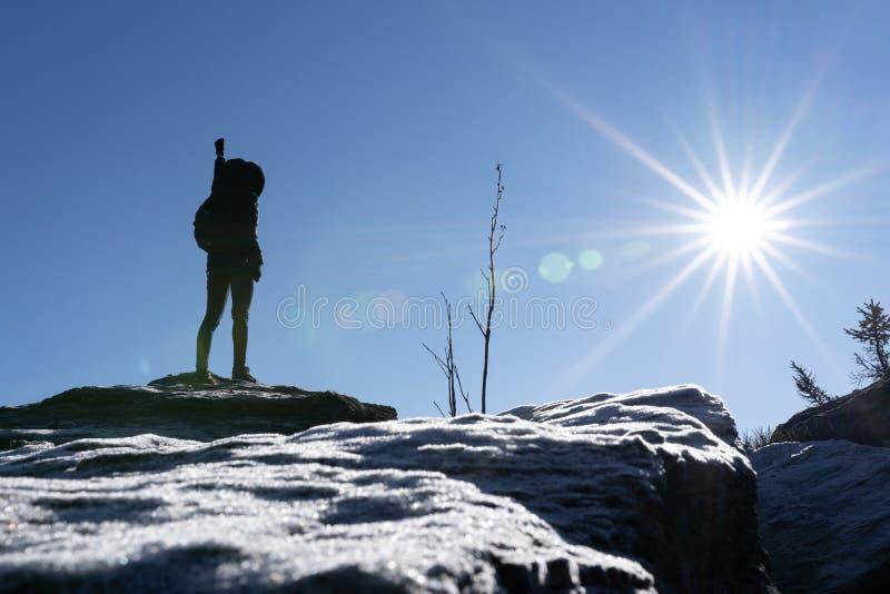 Braços abertos Cheering do caminhante da mulher no pico de montanha retroiluminado com crystalls pesados do lensflare e do gelo n imagens de stock