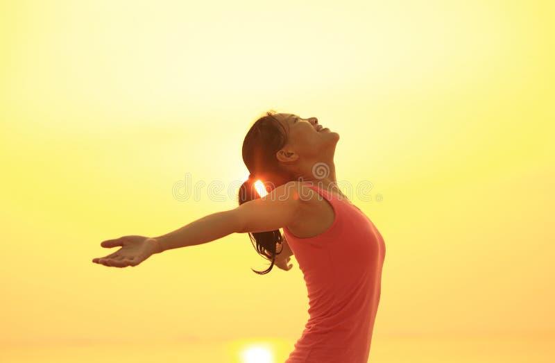 braços abertos da jovem mulher na praia do nascer do sol imagens de stock royalty free