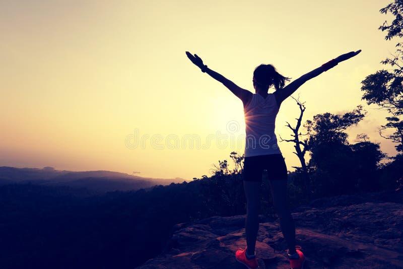Braços abertos da mulher bem sucedida nova no pico de montanha do por do sol foto de stock royalty free