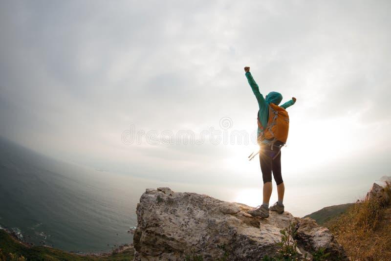 Braços abertos do caminhante bem sucedido da mulher no pico de montanha do beira-mar foto de stock