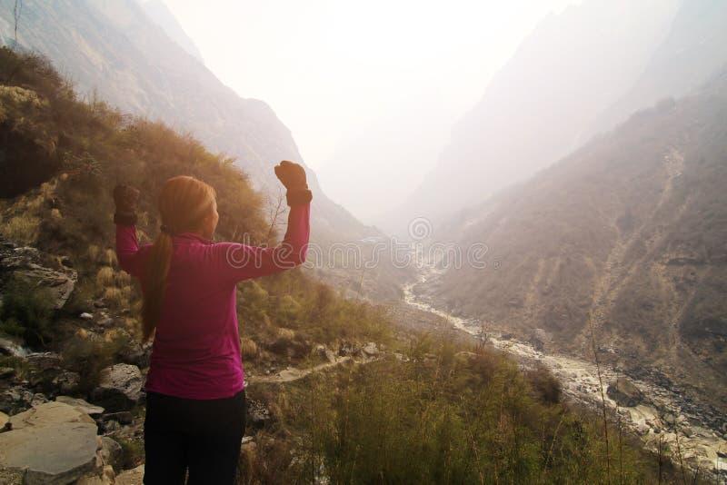 Braços abertos do caminhante da mulher no pico de montanha foto de stock