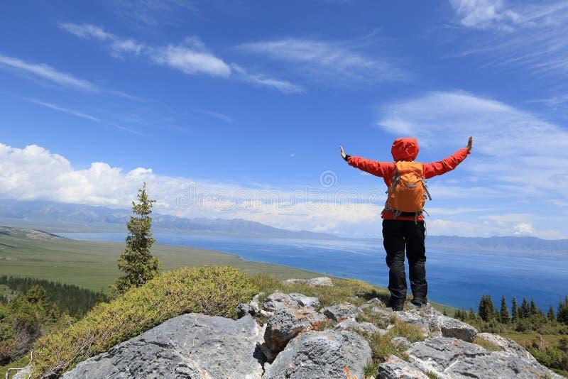 Braços abertos do mochileiro bem sucedido da mulher no pico de montanha fotografia de stock